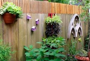 Подойти к вопросу, как украсить забор, можно неординарно – развесьте на нем разноцветные скворечники или горшочки с цветами.