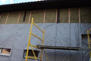 Утепление брусового дома снаружи начинается с вертикальной обрешетки стен